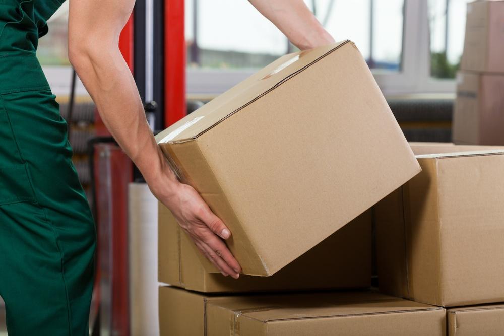 Hands of warehouse worker lifting box, horizontal